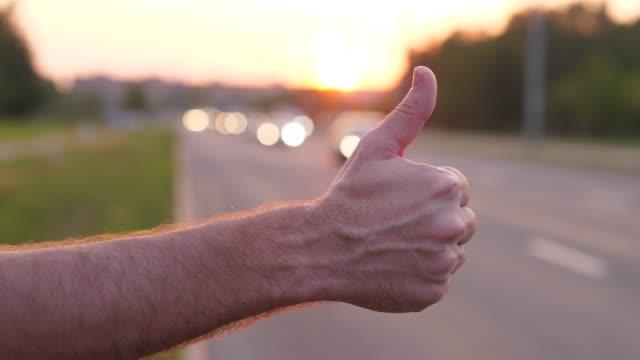De-cerca-para-arriba-pulgar-mano-hombre-autostopista-en-camino-tratar-de-atrapar-el-coche