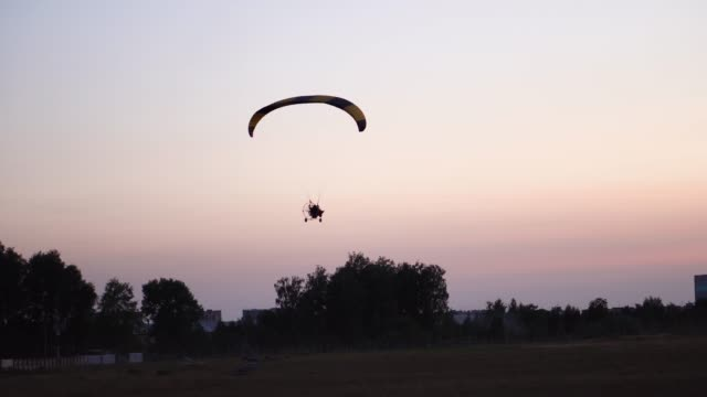 The-pilot-on-a-paraglider-flies-in-the-sky-over-sunset-and-night-landscape-background