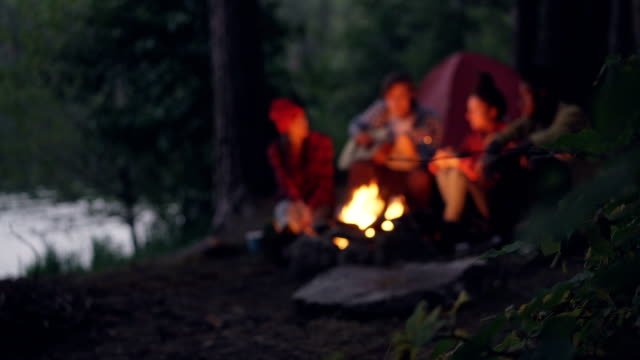 Blurred-footage-of-travelers-romantic-young-people-sitting-near-campfire-in-forest-playing-the-guitar-and-singing-Focus-on-tree-branch-with-leaves-in-foreground-