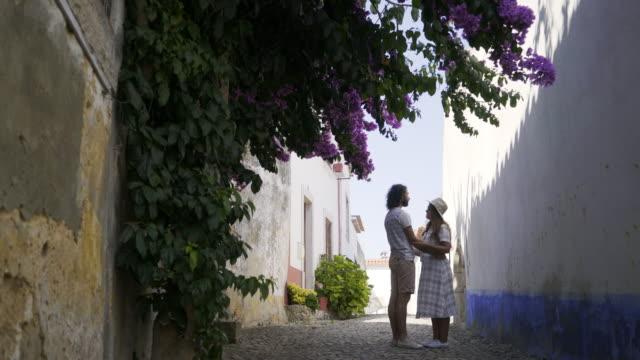 Paar-küssen-zwischen-alten-Gebäuden-in-der-Nähe-von-Strauch-mit-Blüten