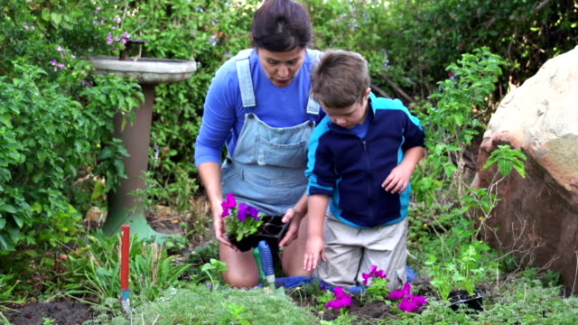Mother-and-child-planting-flower-seedlings-in-the-garden-South-Africa