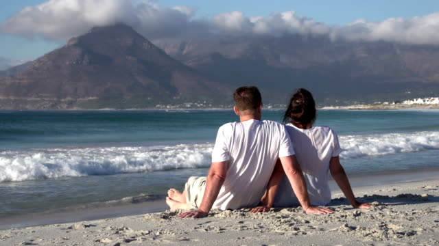 Couple-sitting-close-together-on-beach-and-enjoying-the-view-South-Africa