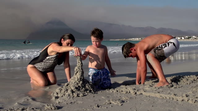 Mother-with-2-children-playing-with-sand-on-beach-Cape-Town
