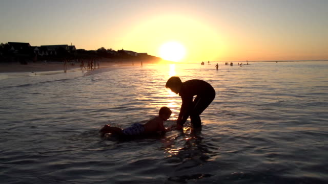 2-young-boys-playing-on-beach-in-silhouette-at-sunset-Cape-Town