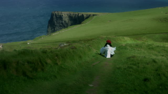 4k-Shot-of-a-Redhead-princess-walking-on-Cliffs-of-Moher-View-in-Ireland