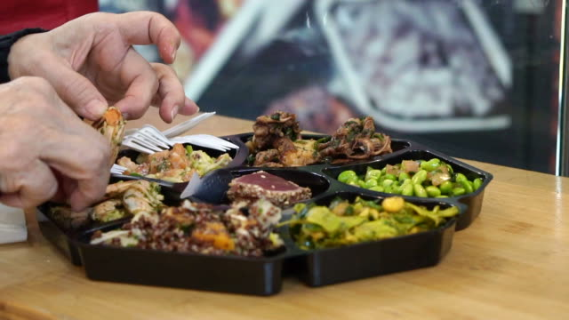 Hand-eating-cold-dish-seafood-and-salad-platter-in-Europe-open-market-shot-in-slow-motion-120-fps