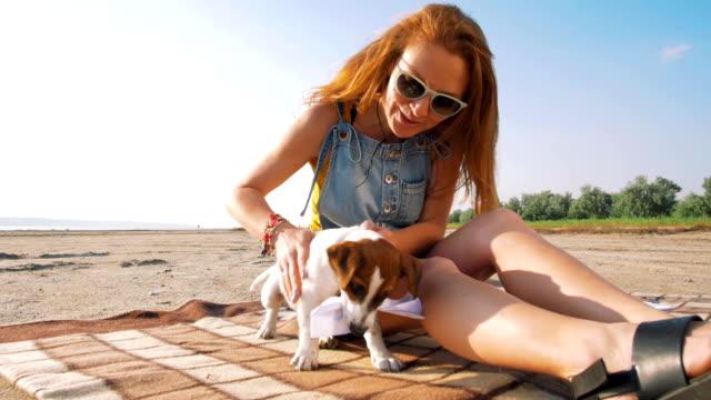 stilvolle-junge-Hipster-spielenden-Hund-Welpen-jack-Russell-am-Strand-Slow-motion