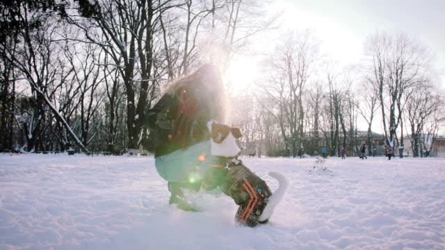 Joven-jugando-con-Jack-Russell-terrier-en-época-de-invierno-en-la-nieve-cámara-lenta