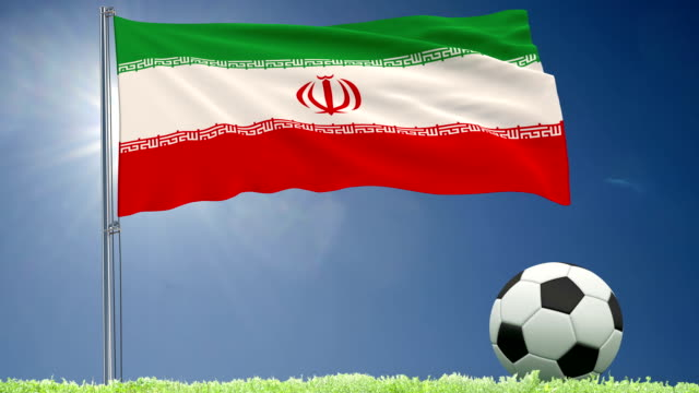Flag-of-Iran-fluttering-and-a-football-rolls-on-the-lawn-3d-rendering-4k-footage