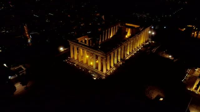 Video-de-noche-aérea-emblemática-antigua-colina-de-la-Acrópolis-y-el-Partenón-por-la-noche-el-centro-histórico-de-Atenas