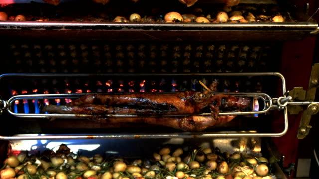 tilt-up-shot-of-a-pig-chickens-and-vegetables-on-a-restaurant-rotisserie-paris