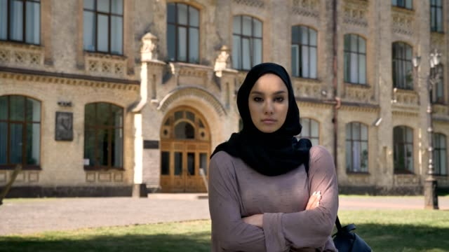 Young-self-confident-muslim-girl-is-standing-with-arms-crossed-in-daytime-in-summer-watching-at-camera-building-on-background-religious-concept