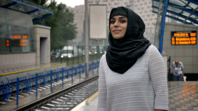 Young-muslim-woman-in-hijab-is-waiting-for-train-n-railway-station-raining-religion-concept-urban-concept-weather-concept