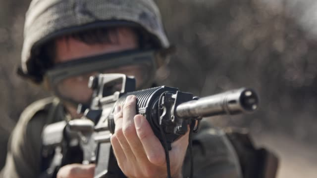 Israeli-soldier-pointing-his-rifle-and-scanning-the-area---close-up