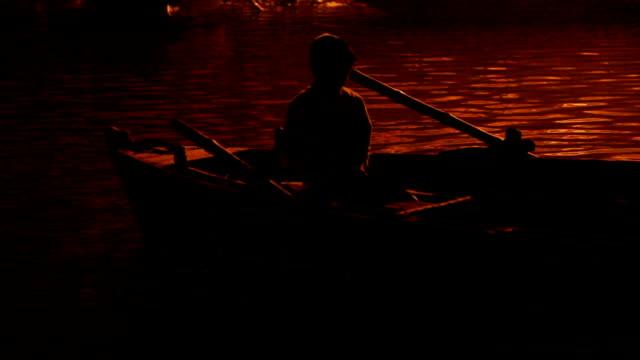 Niño-en-una-embarcación-iluminado-por-luces-de-la-Ghats-por-Ganges:-Varanasí-India