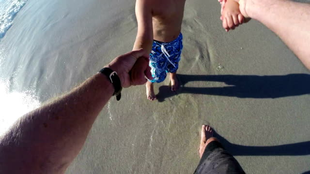 POV-of-Father-swinging-happy-child-on-beach-Cape-Town