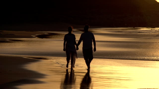Couple-enjoying-romantic-walk-along-the-beach-in-silhouette-Cape-Town-South-Africa
