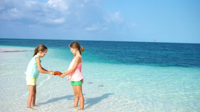 Adorable-little-girls-with-starfishes-on-white-empty-beach