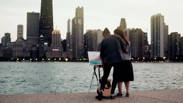 Young-creative-couple-on-the-shore-of-Michigan-lake-Chicago-America-Woman-drawing-man-holding-the-guitar-in-evening