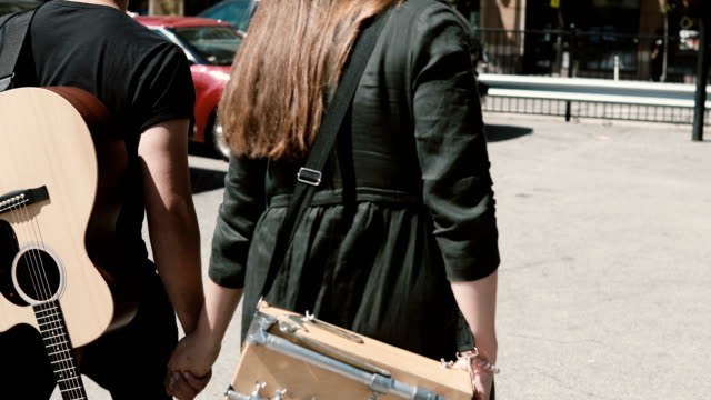 Young-beautiful-couple-walking-in-downtown-together-Chicago-America-Man-holding-guitar-woman-sketchbox