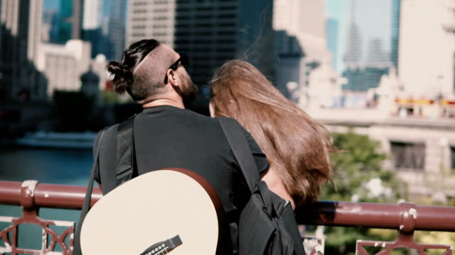 Back-view-of-young-beautiful-couple-standing-on-the-bridge-enjoying-the-view-of-Chicago-America-Man-with-guitar