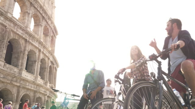 Three-happy-young-friends-tourists-riding-bikes-with-backpacks-at-Colosseum-in-Rome-on-sunny-day-slow-motion-camera-steadycam-ground-shot