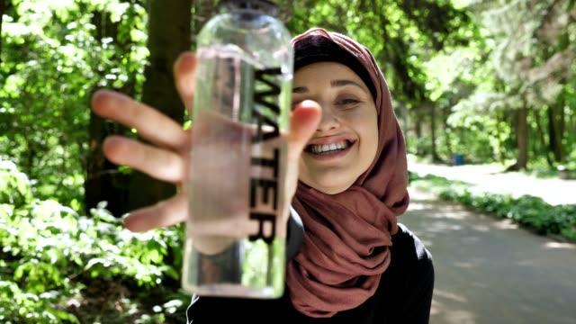 Retrato-de-una-linda-chica-joven-en-un-hiyab-con-una-botella-de-agua-en-sus-manos,-sonriendo,-mirando-a-la-cámara,-parque-en-el-fondo,-enfoque-tire-50-fps