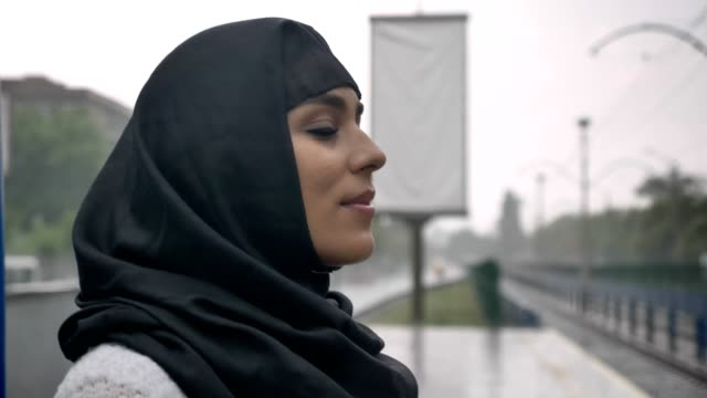 Young-muslim-woman-in-hijab-is-waiting-for-train-on-railway-station-raining-religion-concept-urban-concept-weather-concept-side-view