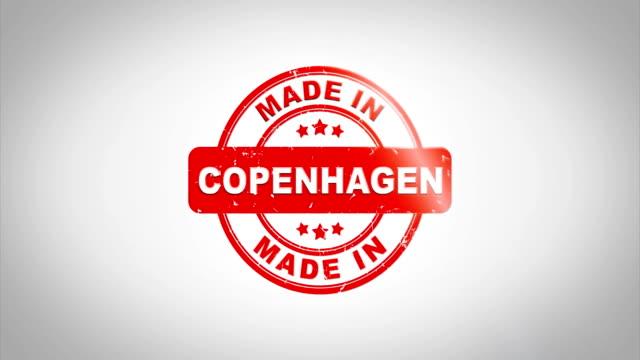 En-Copenhague-firmado-sellado-Sello-madera-animación-de-texto-Tinta-roja-en-el-fondo-de-superficie-de-papel-blanco-limpio-con-verde-mate-fondo-incluido-