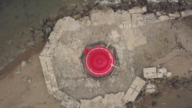 Drohne-Ansicht-oben-rote-Dach-des-Leuchtturm-am-Rand-am-Meer