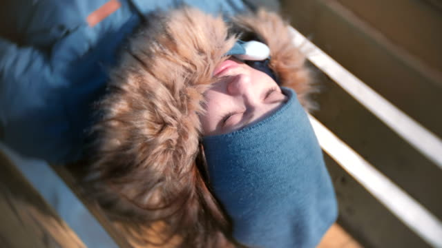 Young-woman-sleeping-in-the-Park-on-a-bench-in-the-winter-Close-up-face-