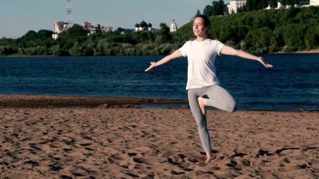 Mujer-de-estiramientos-yoga-en-la-playa-por-el-río-en-la-ciudad-Vista-hermosa-ciudad-Vrikshasana-pose-