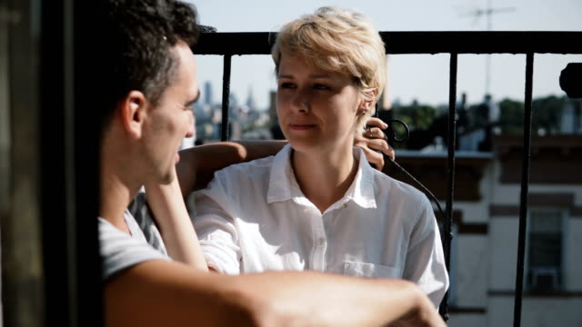 Beautiful-young-European-woman-talking-to-man-Couple-sitting-at-a-small-sunny-apartment-balcony-talking-to-each-other