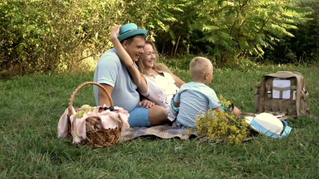 Mom-dad-and-little-son-having-fun-and-playing-hats-on-the-grass-in-the-Park-They-had-a-picnic-in-the-open-air-Vintage-processing-