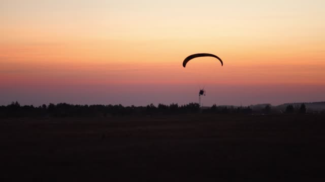 The-pilot-on-a-paraglider-flies-in-the-sky-after-sunset-with-orange-background