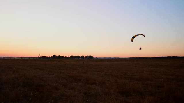 Pilot-flying-a-paraglider-with-a-motor-at-sunset-the-camera-on-the-suspension-moves-along-the-field
