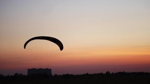 The-pilot-on-the-paraglider-comes-to-land-in-the-field-at-sunset