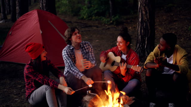 Young-lady-traveler-is-playing-the-guitar-her-friends-are-cooking-food-on-fire-and-African-American-man-is-clapping-hands-Friendship-people-and-music-concept-