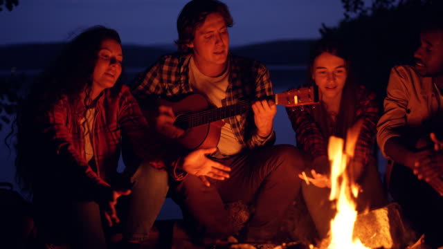 Young-men-and-women-are-singing-songs-to-the-guitar-resting-around-campfire-and-enjoying-music-and-good-company-on-summer-night-Trees-and-lake-are-visible-