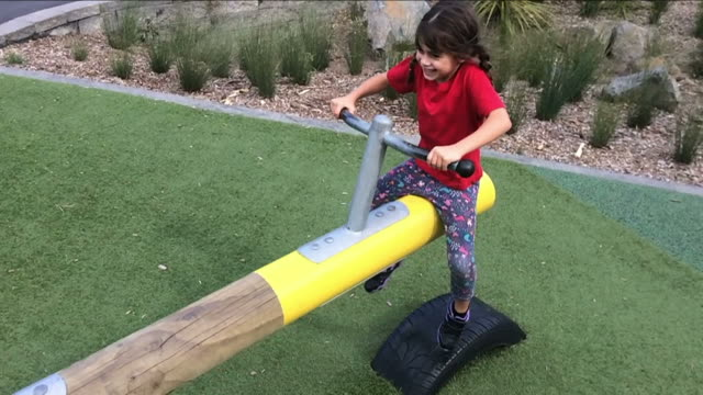 Slow-motion-child-girl-rids-on-Seesaw