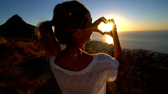 Young-woman-watching-sunset-by-the-sea-makes-heart-shape