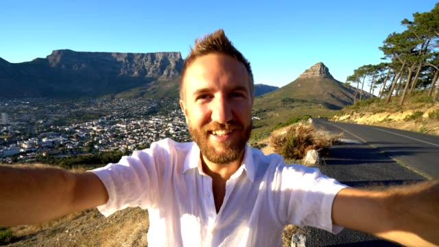 Young-man-taking-selfie-portrait-in-Cape-Town-at-sunrise