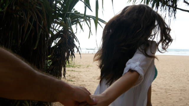 Girl-holding-male-hand-and-running-on-tropical-exotic-beach-to-the-ocean-Follow-me-shot-of-young-woman-pull-her-boyfriend-on-the-sea-shore-Summer-vacation-or-holiday-Point-of-view-POV