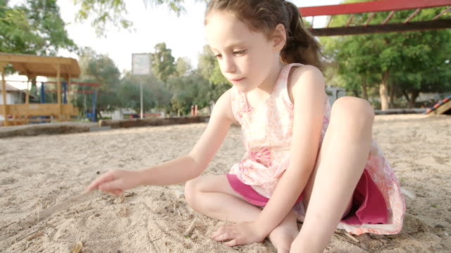 Little-girl-playing-in-a-sandbox-in-a-playground