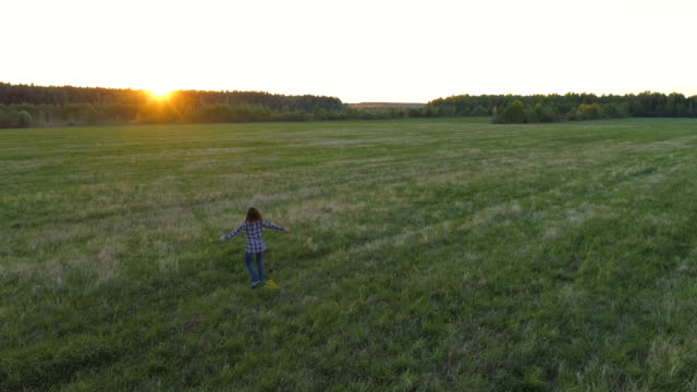 Woman-walking-on-the-field-at-sunset-arms-out-to-the-sides-with-flowers-in-her-hand-