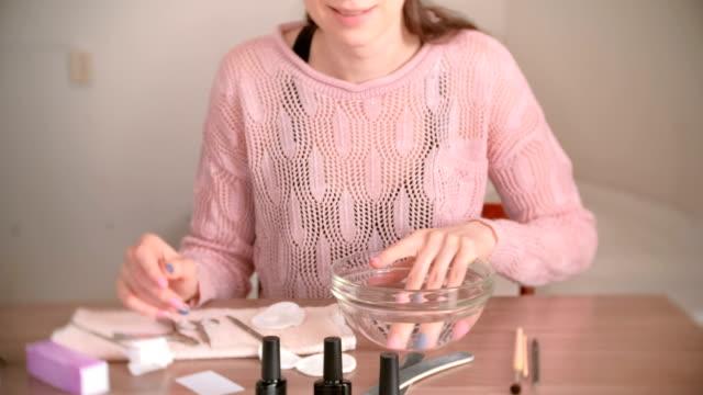 Manicura-en-casa-Mujer-que-sumerge-su-mano-en-un-recipiente-de-agua-Herramientas-sobre-la-mesa-de-manicura-