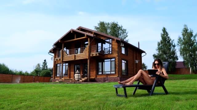 Schöne-schlanke-Frau-liegend-auf-einer-Sonnenliege-in-einem-Badeanzug-mit-einem-Tablet-auf-dem-Hintergrund-eines-großen-Landhauses-in-Sonnenbrillen