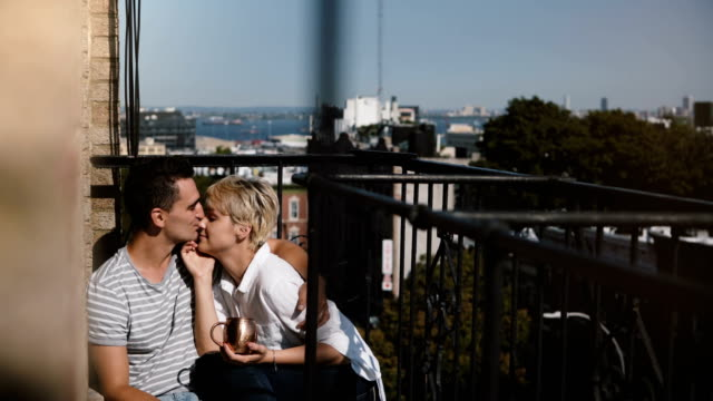 Happy-relaxed-multiethnic-romantic-couple-sitting-close-together-at-a-lovely-sunny-morning-balcony-in-New-York