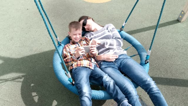 Mom-and-son-swinging-on-empty-webbed-swing-and-playing-game-on-mobile-phone-together-