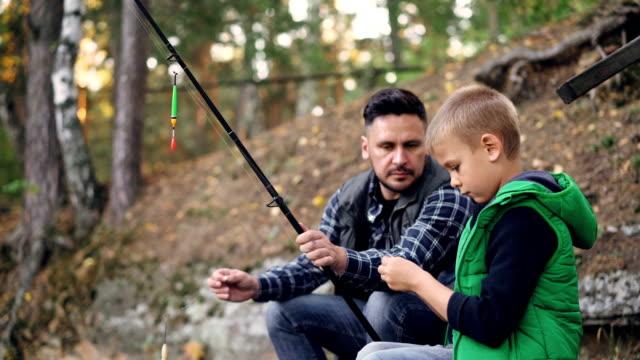 Padre-e-hijo-son-barras-de-explotación-de-pesca-y-hablar-hombre-enseña-niño-utilizar-equipo-en-día-de-otoño-con-árboles-a-su-alrededor-Concepto-de-familia-hobby-y-ocio-